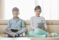 Cute siblings using technologies on sofa at home