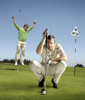 Full length portrait of golfer lining up shot with man jumping in background