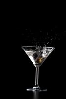 Splash in mrtini glass on black background 11044031774| 写真素材・ストックフォト・画像・イラスト素材|アマナイメージズ