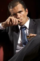Portrait of young man smoking cigar and holding wineglass