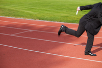 Businessman running on race track