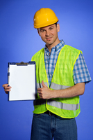 Portrait of architect holding clipboard and showing thumbs up sign