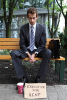 young caucasian businessman in park with executive for rent sign