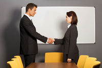 Businessman and woman shaking hands in office, smiling