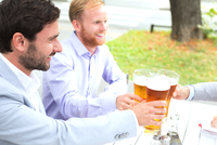 Businessmen toasting beer glasses with female colleague at outdoor restaurant 11044034283| 写真素材・ストックフォト・画像・イラスト素材|アマナイメージズ