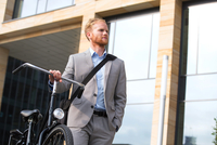 Businessman with bicycle looking away while standing outside office building