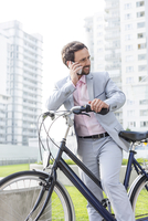 Businessman answering mobile phone while standing with bicycle outdoors