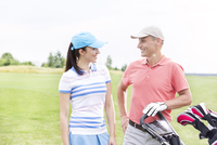 Happy male and female golfers communicating against clear sky