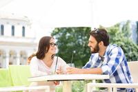 Smiling couple having mojito at sidewalk cafe