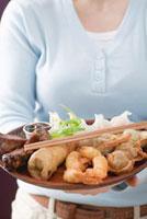 Woman holding Asian appetiser platter
