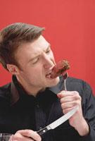 Man biting a tough piece of beef steak