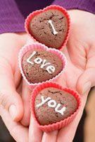 Hands holding chocolate buns for Valentine's Day 11047032475| 写真素材・ストックフォト・画像・イラスト素材|アマナイメージズ