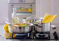 Vegetables and spaghetti in pans on a gas cooker