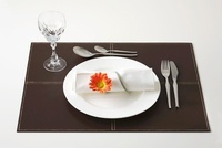 Place-setting with napkin and artificial gerbera on table ma