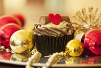 A gold cupcake with a heart and baubles