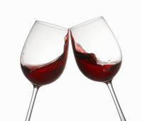 Glasses of red wine being clinked together