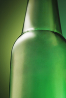 Green Beer Bottle on a Green Background; Close Up