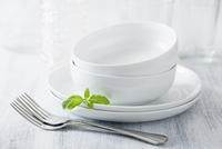 Two dinner bowls with plates and forks