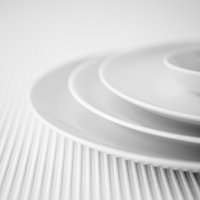 Closeup of a stack of three white plates and a small dish