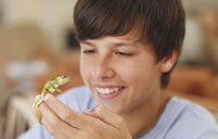 Boy holding lizard smiling