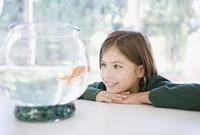 Girl looking at goldfish in bowl