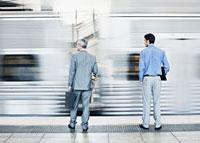 Businessmen watching speeding train