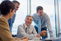 Smiling business people using laptop in meeting