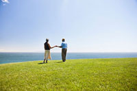 Senior couple holding hands on grassy hill overlooking ocean