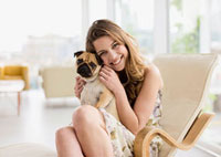 Smiling woman holding cute,small dog on lap