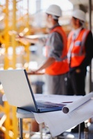 Construction workers behind laptop and blueprints on constru