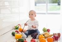 Baby making mess on floor with food