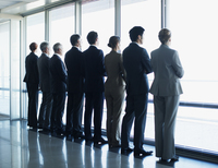 Business people standing in a row and looking out window