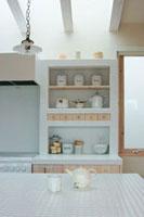 キッチンのテーブルに置かれたティーポットとカップと食器棚