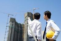 建設中のビルを見る2人の若いビジネスマン