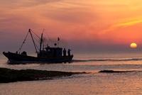 夕日と漁船のシルエット