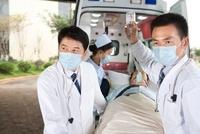 救急車から患者を運ぶ医師たち