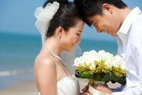 ビーチで見つめ合う新婚カップル