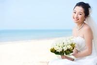 ビーチにたたずむウェディングドレス姿の花嫁
