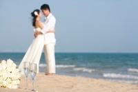 ビーチで抱き合う新婚カップル