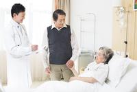 入院中の妻を見舞う男性と医師