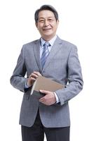 本を持つスーツ姿のシニア男性