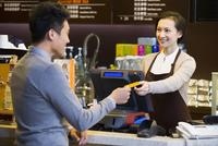 カフェで会計をする女性と店員