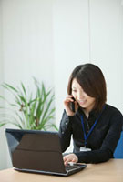 パソコンを見ながら携帯で話す女性