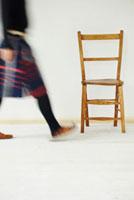 歩く女性と木製のイス
