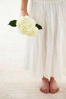 白い花を持つ裸足の女性