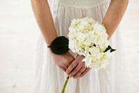 白い花を持つ女性の手元