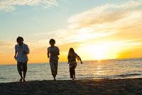 夕日が沈む海と砂浜を走る若者たち
