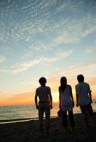 夕日が沈む海を見つめる若者たち