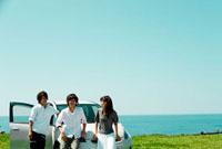 海辺に停めた車と若者たち