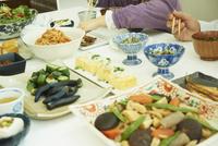 食卓に並んだ料理と食事をする子供と父親の手元